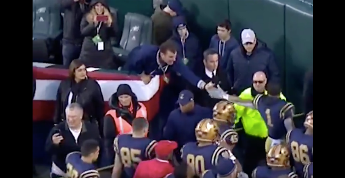 Fan falls out of stands while trying to high-five Navy player